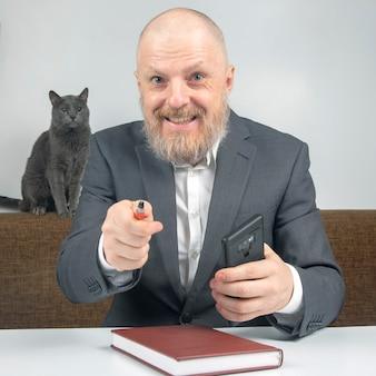 Biznesmen i szary kot w domowym biurze, pracy z dokumentami.