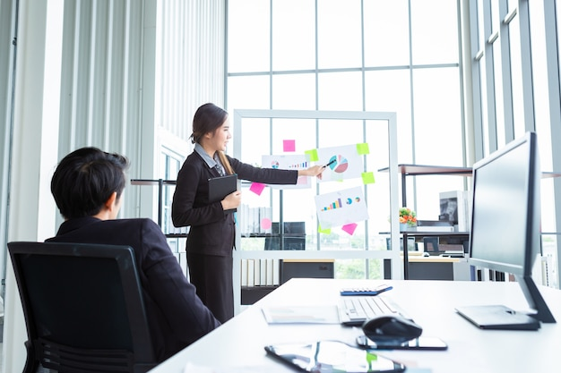 Biznesmen i szef bizneswoman dwóch partnerów przedstawiających nowe pomysły na projekty i wzrost liczby otrzymanych bransoletek w biurze, trenerka przedstawiająca udany biznesplan