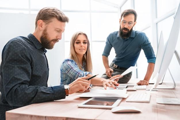 Biznesmen i uśmiechnięci pracownicy sprawdzanie sprawozdania finansowego. pojęcie pracy zespołowej