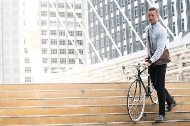 Biznesmen idzie do pracy na rowerze.