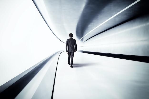 Biznesmen idzie w futurystycznym stalowym tunelu