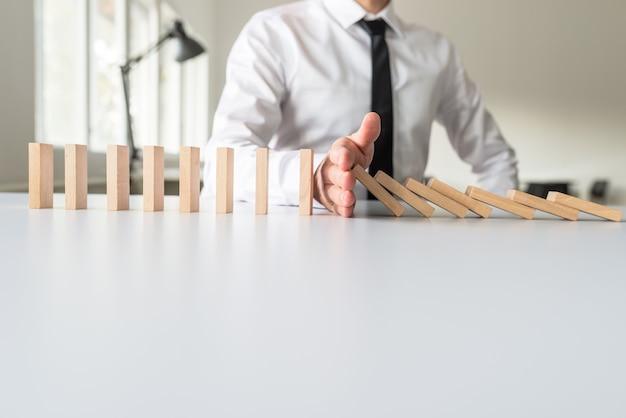 Biznesmen interweniuje, aby zatrzymać spadające domino ręką w obrazie koncepcyjnym.