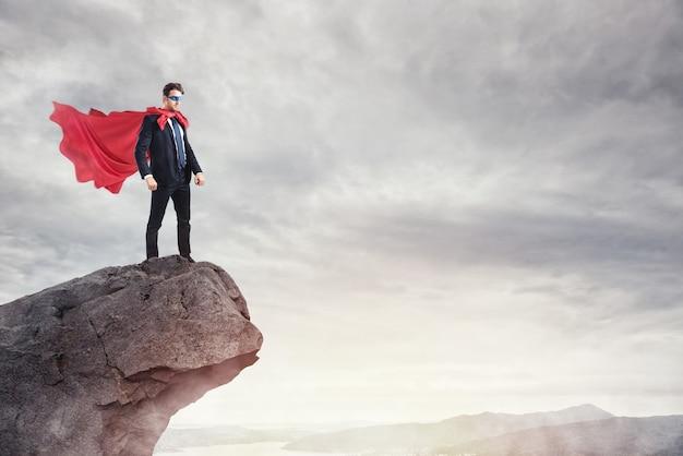 Biznesmen jako superbohater na szczycie góry