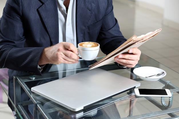 Biznesmen jedzący lunch i pracujący w kawiarni, zbliżenie