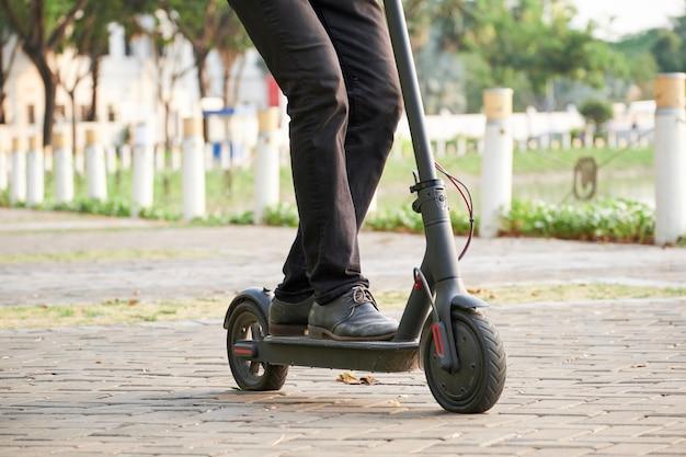 Biznesmen jedzie na cooter w parku
