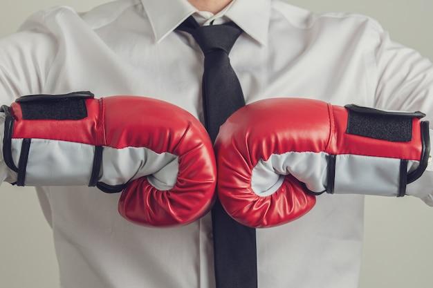 Biznesmen jest ubranym czerwonego boks wpadać na siebie jego pięści razem