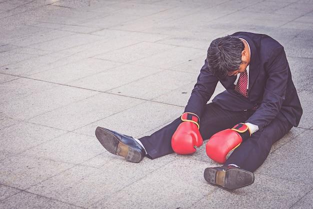 Biznesmen jest ubranym czerwonego bokserskiego rękawiczki obsiadanie na podłoga ale czuciowym stresie o pracie.