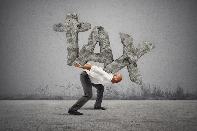 Biznesmen jest uciskany ciężarem podatków