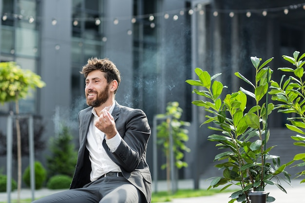 Biznesmen kaukaski brodaty mężczyzna palenia konopi na zewnątrz siedzi na ławce w parku miejskim na tle ulicy miejskiej. mężczyzna pracownik biznesmen. pracownik biurowy w garniturze łagodzi stres związany z marihuaną na zewnątrz
