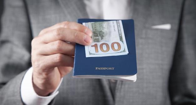 Biznesmen kaukaski gospodarstwa paszport i banknot dolar.
