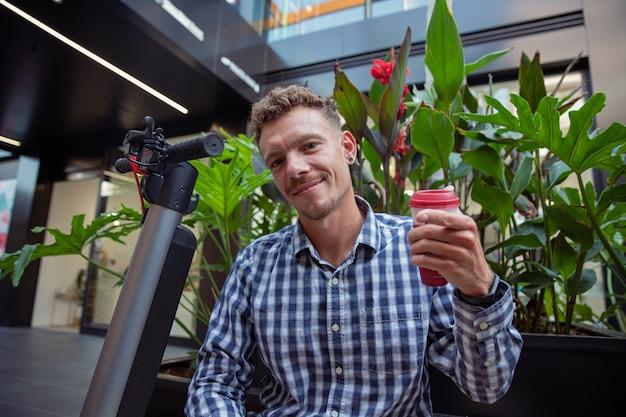 Biznesmen kaukaski ubrany w koszulę w kratę pije kawę siedząc na ławce swoim skuterem elektrycznym. uśmiechnięty milenijny chłopiec wskazuje palcem na aparat - koncepcja zrównoważonej mobilności