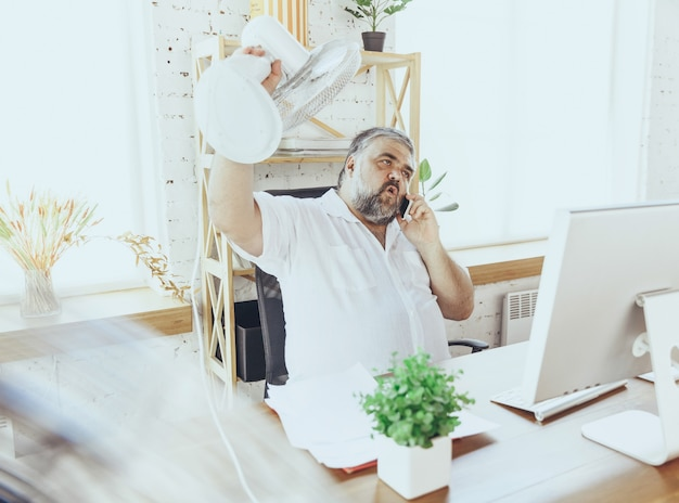 Biznesmen, kierownik czuje się gorąco w biurze