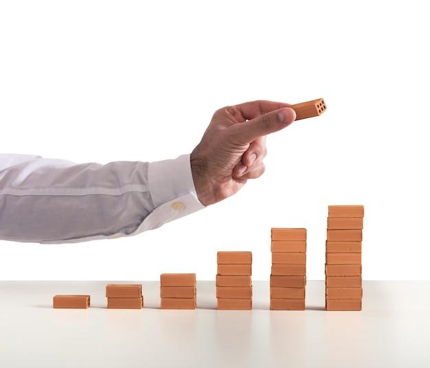 Biznesmen kładzie cegłę na cegły wykonane statycznie. pojęcie rosnących statystyk i sukcesu