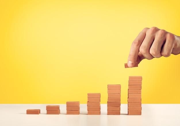 Biznesmen kładzie cegłę na stos cegieł. pojęcie rosnących statystyk i sukcesu. żółte tło