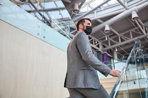 Biznesmen kładzie rękę ze smartfonem na poręczach