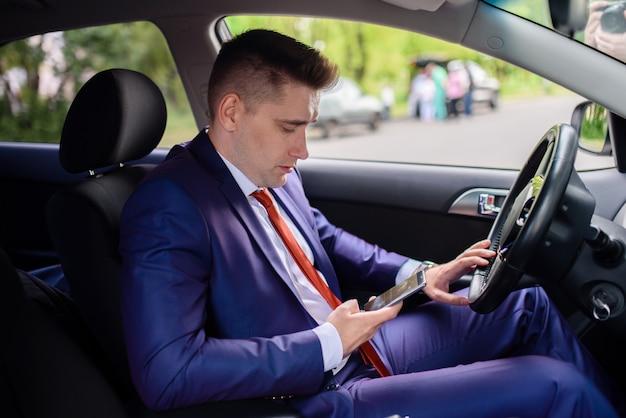 Biznesmen komunikuje się przez telefon w samochodzie.