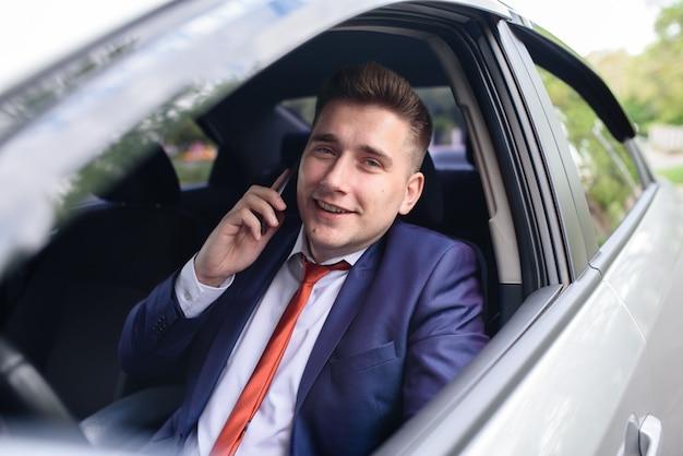 Biznesmen komunikuje się telefonicznie w samochodzie