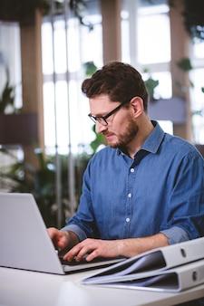Biznesmen koncentruje się na laptopie przy kreatywnie biurem