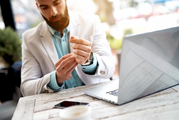 Biznesmen konfigurowania inteligentnego zegarka pod ręką.
