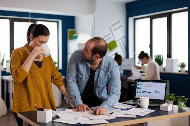 Biznesmen konsultingu start up z doradcą patrząc na statystyki wykresów. zróżnicowany zespół ludzi biznesu analizujących z komputera raporty finansowe firmy. udany start korporacyjny zawód