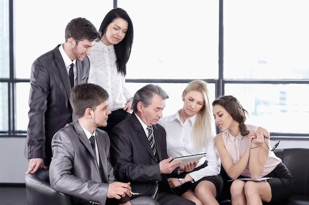 Biznesmen korzysta z cyfrowego tabletu na spotkaniu roboczym z pracownikami