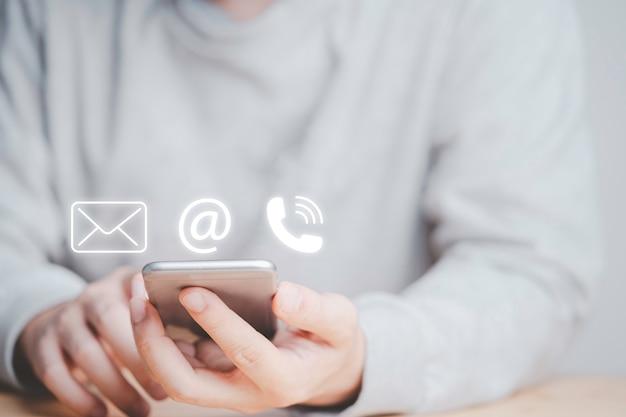 Biznesmen korzystający ze smartfona do kontaktu biznesowego na stronie internetowej zawiera adres e-mail i numer telefonu