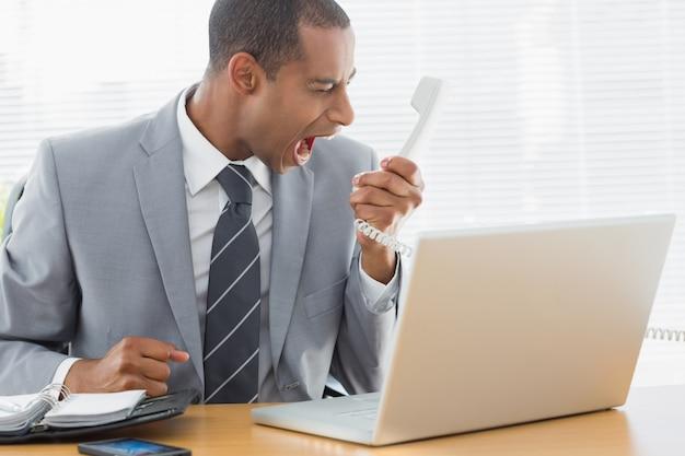 Biznesmen krzyczy w telefon przy biurem