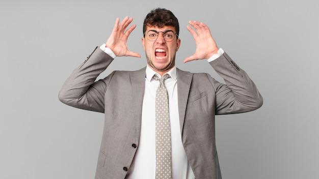 Biznesmen krzyczy z rękami w górze, czuje się wściekły, sfrustrowany, zestresowany i zdenerwowany