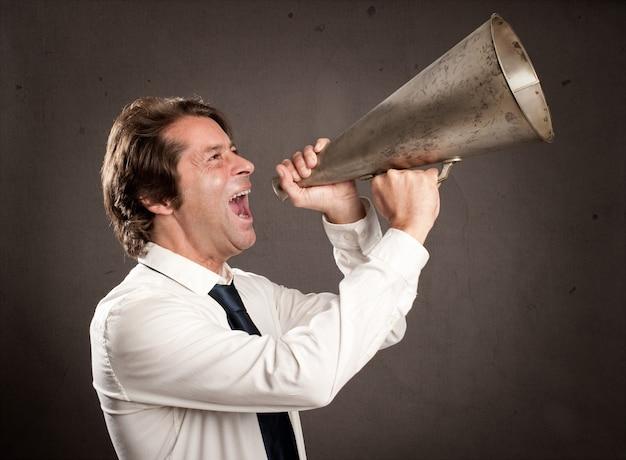 Biznesmen krzyczy z starym megafonem