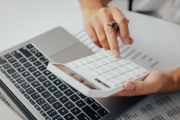 Biznesmen księgowy pracujący nad analizą danych dotyczących inwestycji w nieruchomości za pomocą kalkulatora