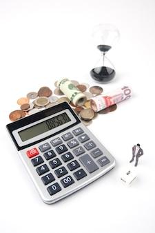Biznesmen, który patrzy na kości z kalkulatorem elektronicznym i pieniądze z białym