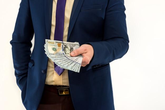 Biznesmen kupuje lub wynajmuje produkt lub usługę, dając dolarów, na białym tle. męska ręka oferuje łapówkę