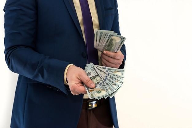 Biznesmen kupuje lub wynajmuje produkt lub usługę, dając dolarów, na białym tle. męska ręka oferuje łapówkę.