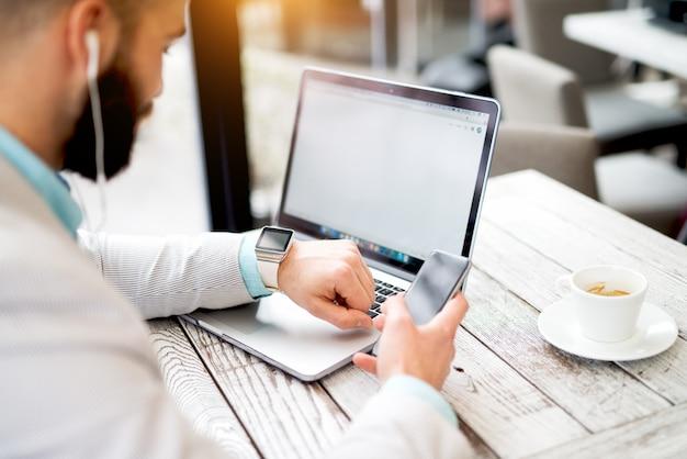 Biznesmen laptop pracuje nad utworzeniem ręki inteligentny telefon inteligentny zegarek