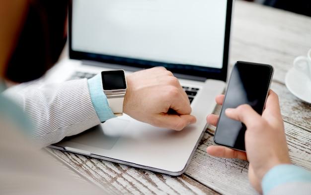 Biznesmen laptop pracuje nad utworzeniem ręki inteligentny zegarek