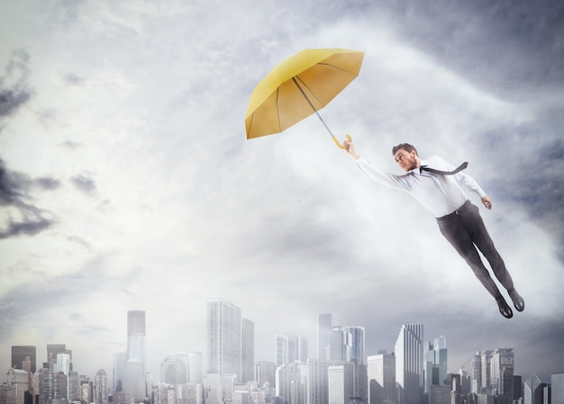 Biznesmen latający z parasolem nad miastem