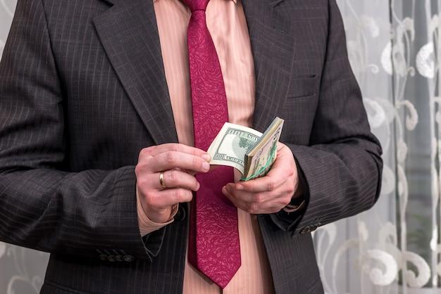 Biznesmen liczący banknoty dolarowe w rękach