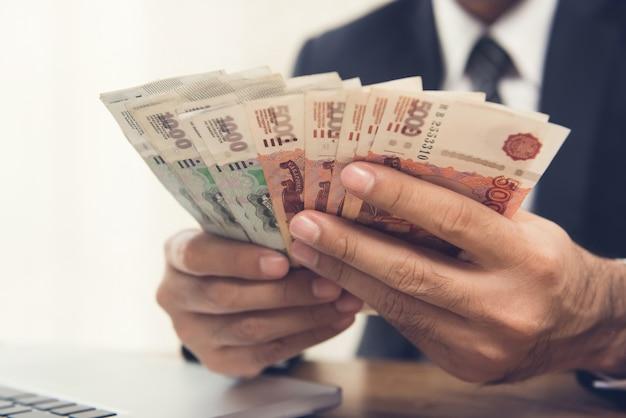 Biznesmen liczenia pieniędzy, waluty rubel rosyjski, przy swoim biurku