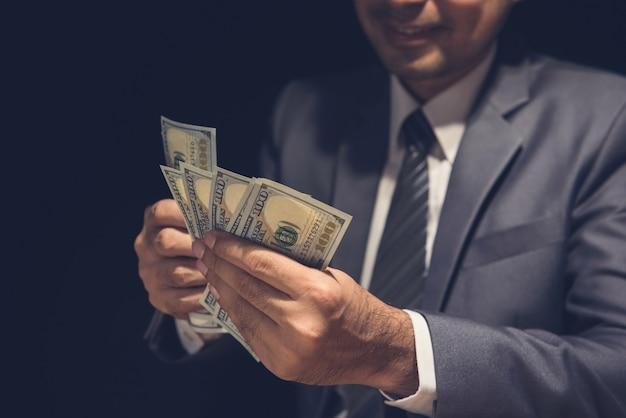 Biznesmen liczenie pieniędzy, rachunki w dolarach amerykańskich, w ciemności