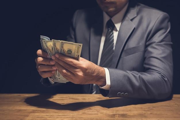 Biznesmen liczy dolary amerykańskie w prywatnym pokoju.