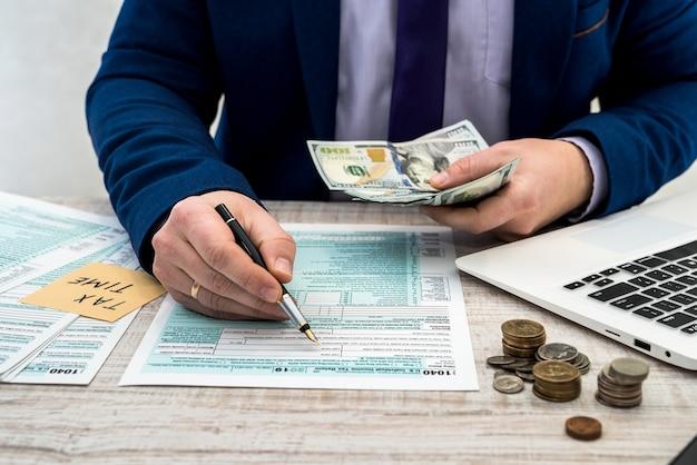 Biznesmen liczy dolary i wypełnia indywidualny formularz podatkowy 1040 us. naklejka z czasem podatku napis. pojęcie podatku.
