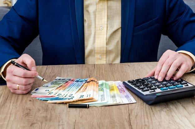 Biznesmen liczy euro za pomocą kalkulatora