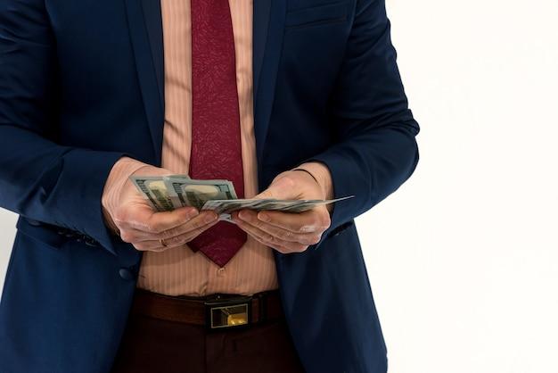 Biznesmen liczy pieniądze na białym tle. mężczyzna w garniturze osiąga zysk lub wygrywa. konto dolarów. koncepcja bogactwa
