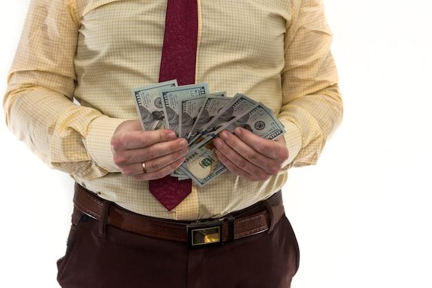 Biznesmen liczy pieniądze na białym tle na białej ścianie