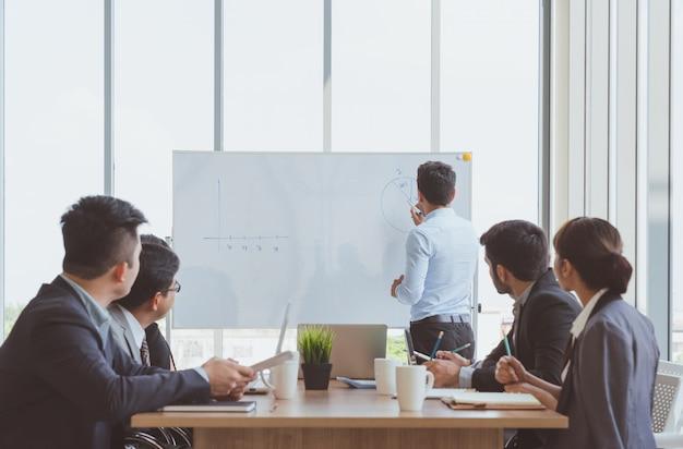 Biznesmen lider pisania na wykresie obecny biznes marketing tablicy podczas spotkania z kolegami w biurze. prezentacja spotkania zespołu biznesowego, koncepcja biznesowa planowania konferencji