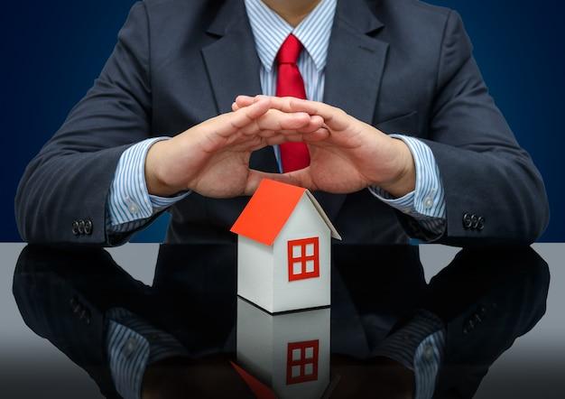 Biznesmen lub agent nieruchomości i trzyma dom modelu