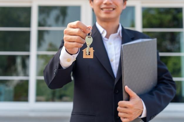 Biznesmen lub agent sprzedaży domu z radością przekazuje klucze do domu nowemu właścicielowi. nowe pomysły na przeprowadzkę, wynajem domu i sprzedaż domu.