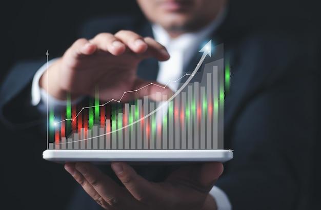 Biznesmen lub handlowiec pokazuje rosnący zapas wirtualnych hologramów. , planowanie i strategia, giełda, rozwój firmy, koncepcja postępu lub sukcesu. , inwestuj w handel.
