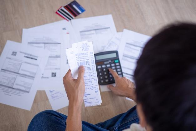 Biznesmen lub kamerdyner siedzi przy prasie różnych kalkulatorów wydatków na fakturach i zadłużeniu na kartach kredytowych. mężczyźni są zestresowani długiem do spłacania co miesiąc. koncepcja zadłużenia