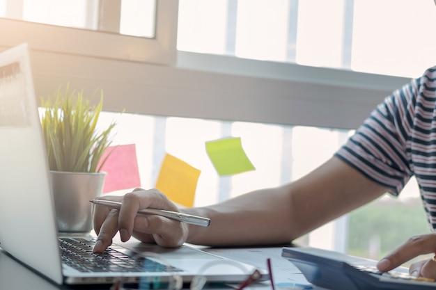 Biznesmen lub księgowego ręki trzymającej pióro działa na komputerze przenośnym do obliczania danych biznesowych